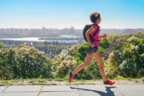 Woman runner run commutes to work with backpack, city morning run commuting and fitness concept, Kiev, Ukraine