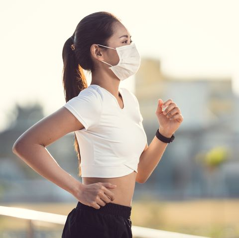 woman runners morning exercise she wears a nose mask protection against dust and viruses
