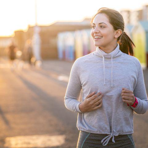 WOMAN RUNNING ALONG BEACHFRONT