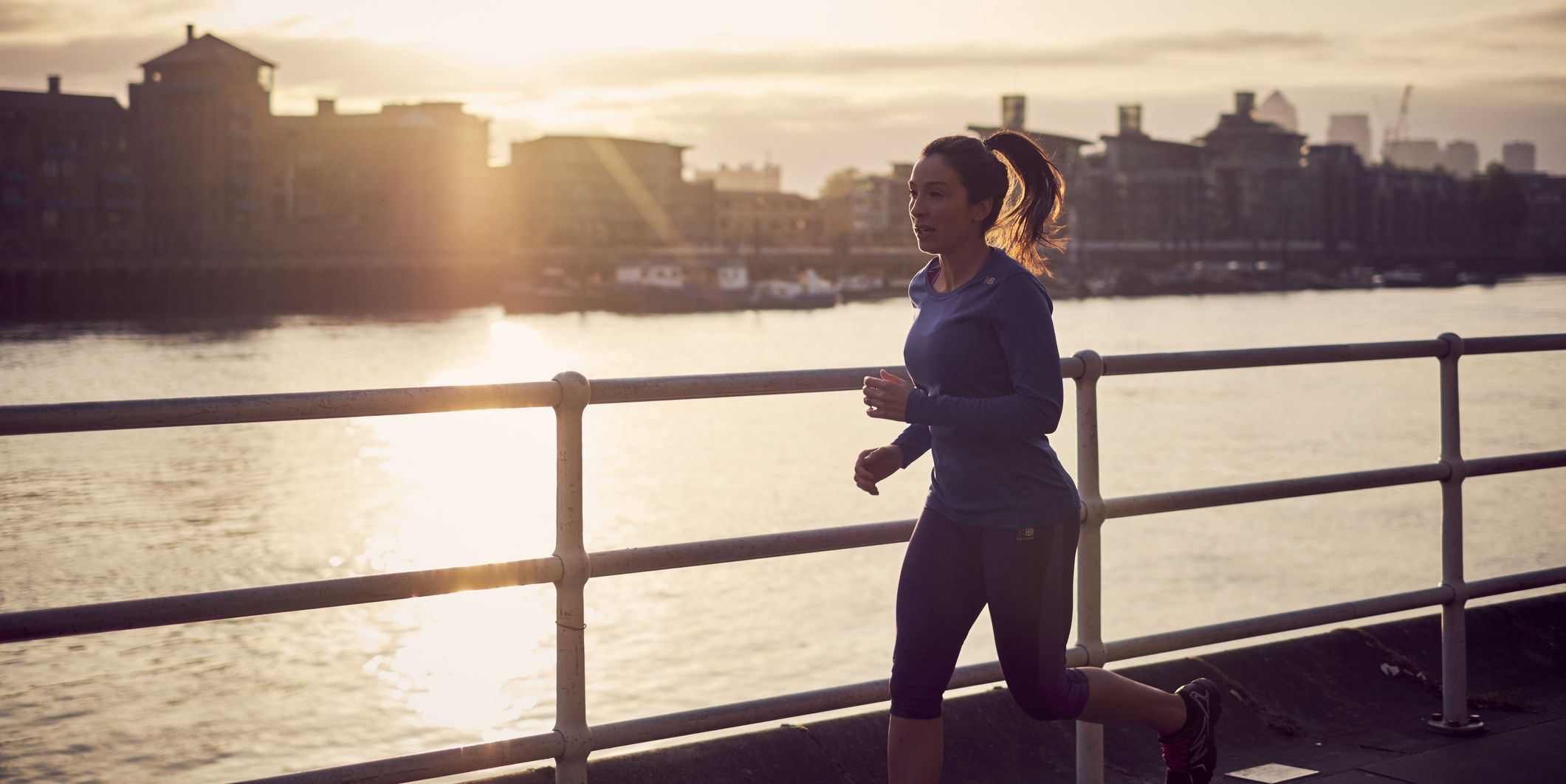 A woman running alongside the River Thames in London