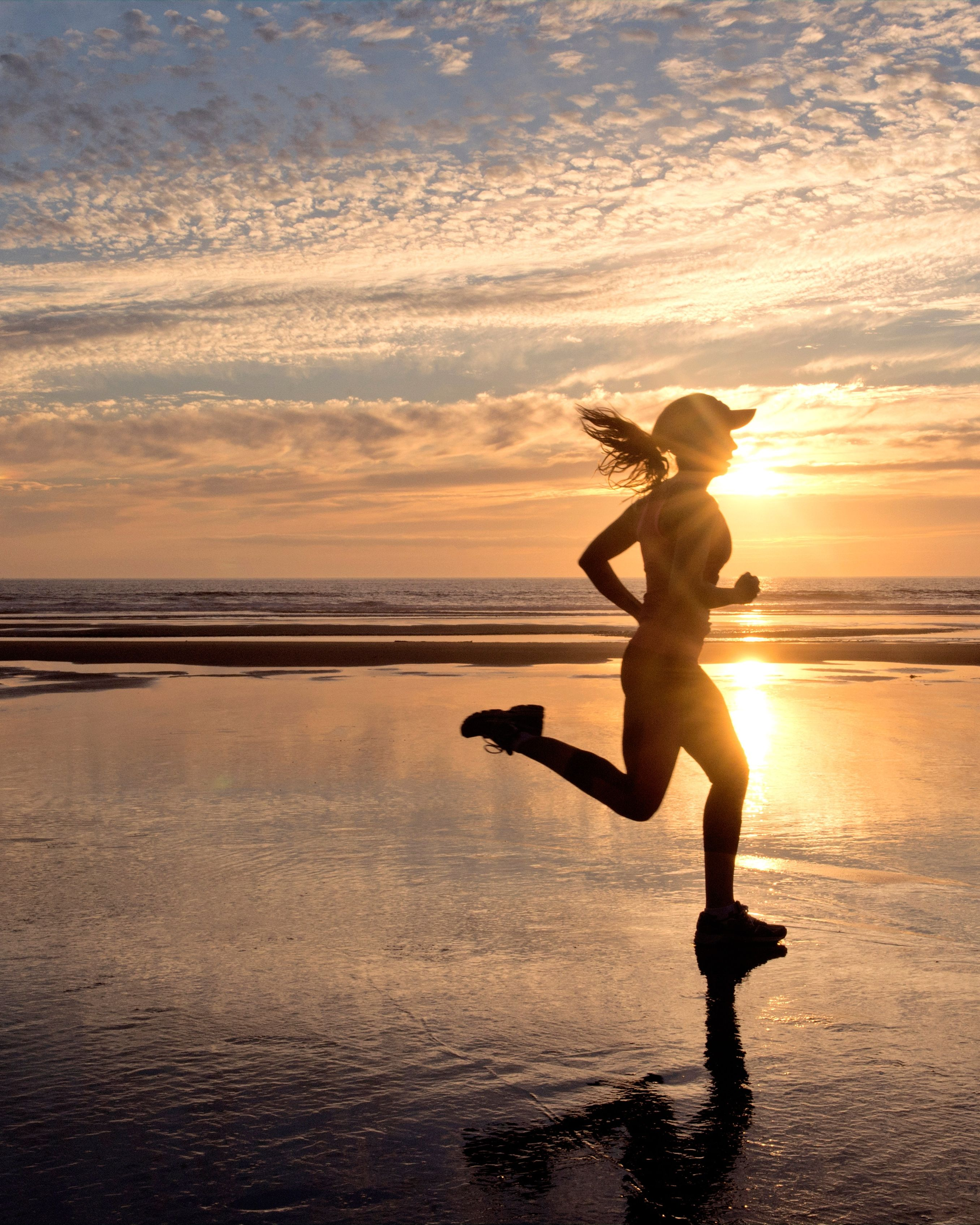 Woman running on beach at sunrise