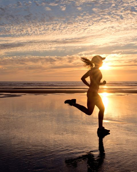 Woman running on beach at sunrise