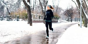 Woman Running On Snowy Field Against Bare Trees