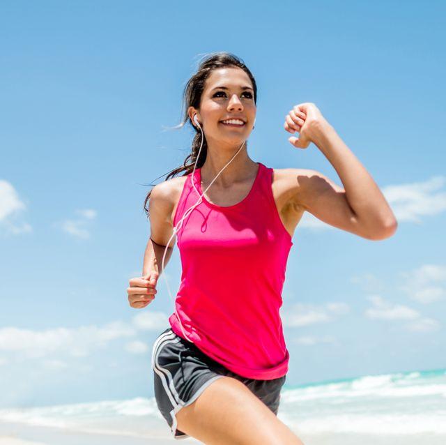 vrouw in een roze sportshirt aan het hardlopen op het strand
