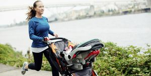 Woman running with baby stroller on footpath by river in city