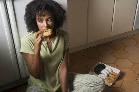 woman seated on kitchen floor at night eating doug