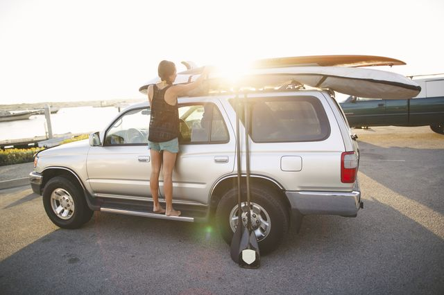 woman secures paddle boards on vehicle, marina