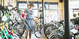 Woman selecting bicycle from rack in bicycle shop