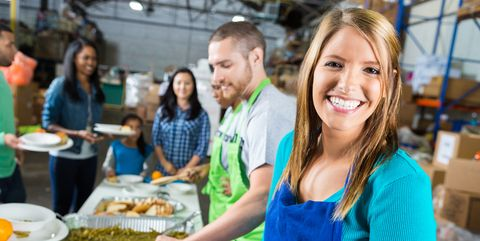 Woman serves food in community soup kitchen