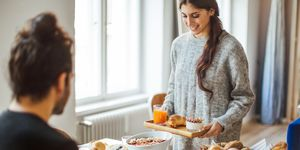 Woman serving breakfast to boyfriend at table