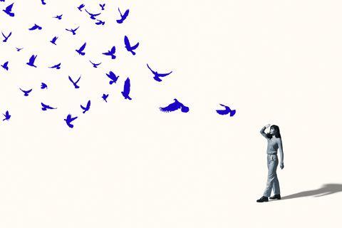 woman shielding eyes in front of flying blue birds