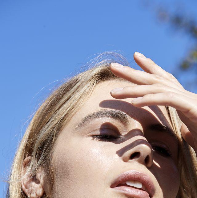 woman shielding her face from sun