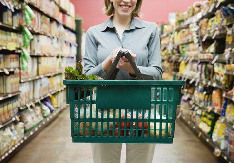 una mujer sostiene una cesta con productos saludables