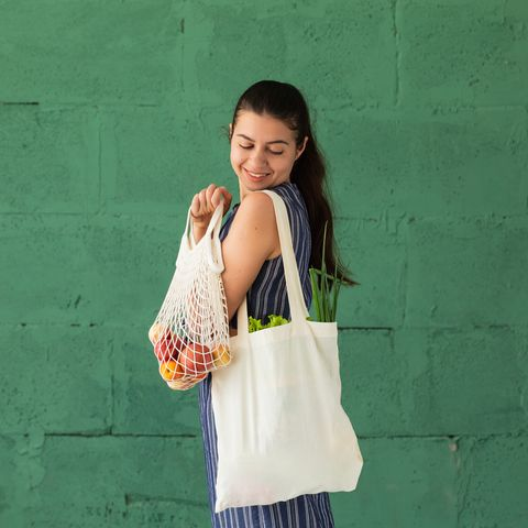 woman shopping fruits and vegetables with reusable cotton eco produce bag zero waste lifestyle concept
