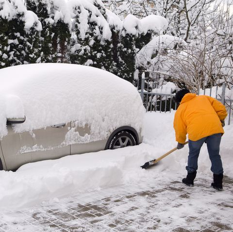 Woman shovelling around snow covered car