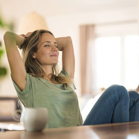 woman sitting at dining table at home relaxing