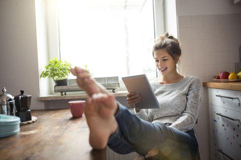 Mujer viendo una tablet en la cocina