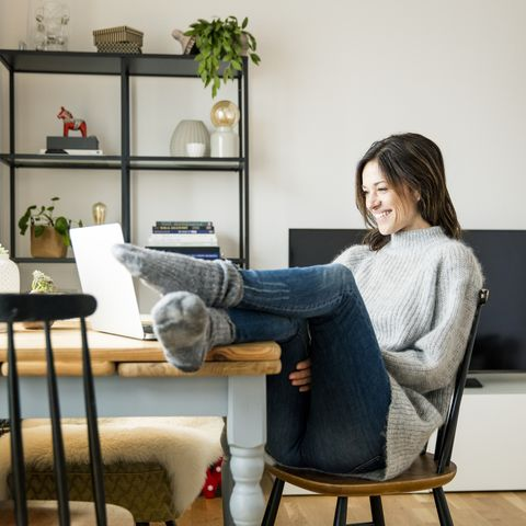 virtual birthday party - Woman sitting at table with feet up, using laptop