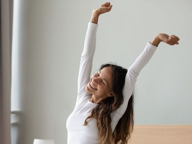 woman sitting in bed stretching her arms muscles after sleep