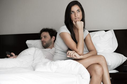 Woman sitting in bed while husband watching tv