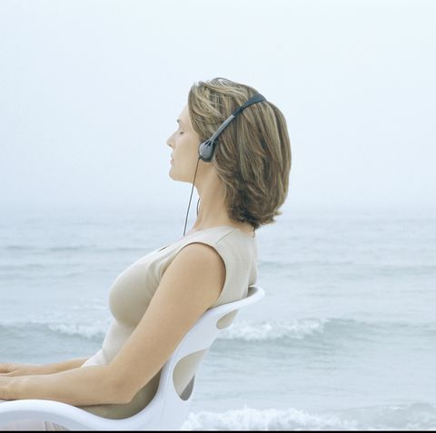 woman sitting in chair, listening to headphones, sea in background