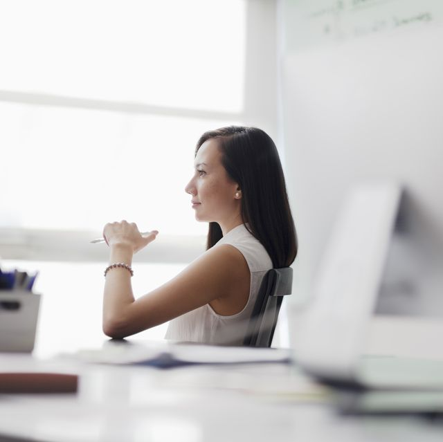 woman sitting in chair looking out office window