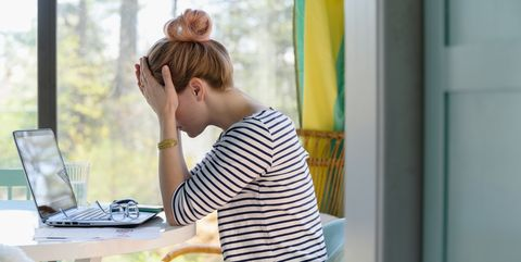 woman sitting in front of laptop with head in hands