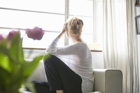 Woman sitting in front of window looking out