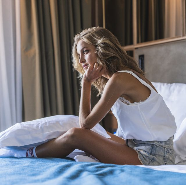 woman sitting on bed in hotel room, looking lonely