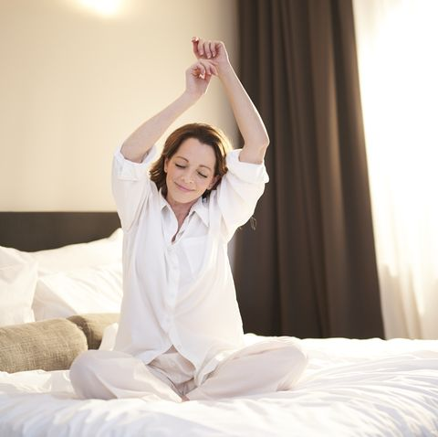 woman sitting on bed stretching