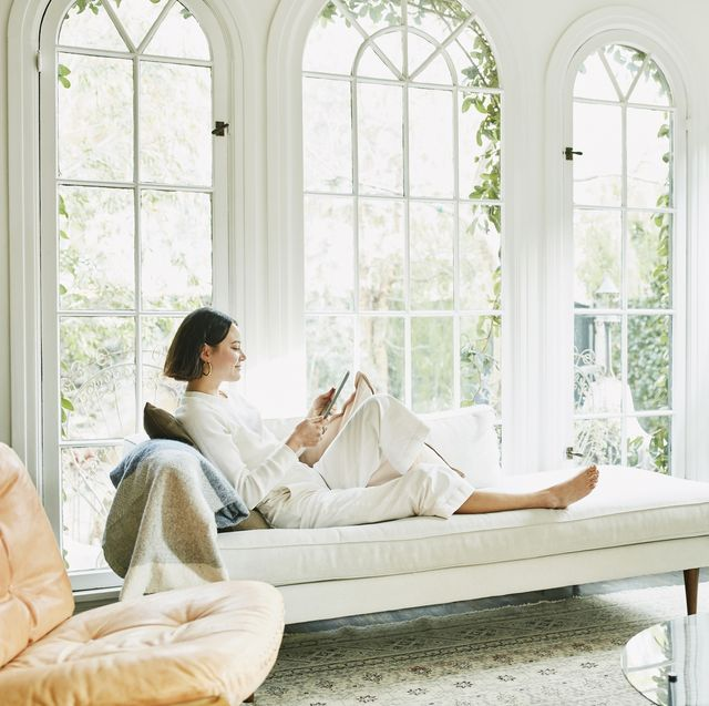 woman sitting on couch in living room reading on digital tablet