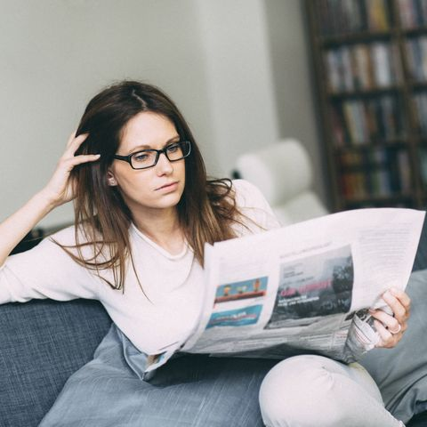 Woman sitting on couch reading newspaper