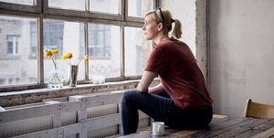 Woman sitting on desk in loft looking through window