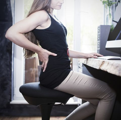 Woman sitting on health chair at desk holding her back