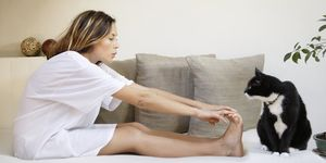 Woman sitting on sofa touching toes, side view