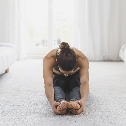 Woman sitting on the floor practicing yoga