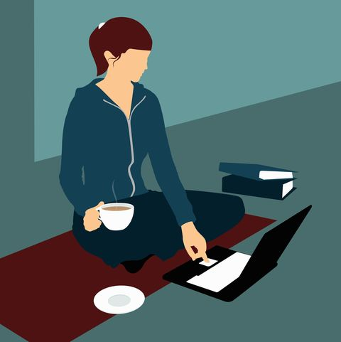 A woman sitting on the floor with a cup of tea and using a laptop