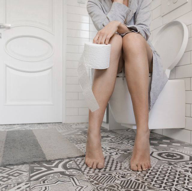 woman sitting on the toilet holding toilet paper
