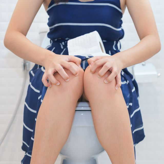 woman sitting on toilet with toilet paper in pain
