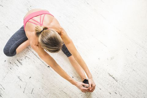 Woman sitting on wooden floor stretching leg