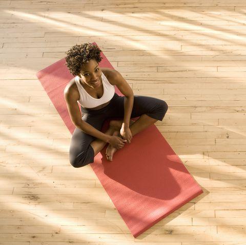 woman sitting on yoga mat