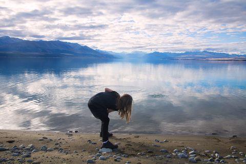 Girl skimming stones at Lake Pukaki, Mount Cook