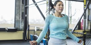 Woman skipping with jumping rope in gym