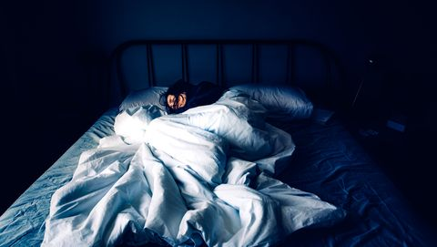 A woman sleeping in bed at night time