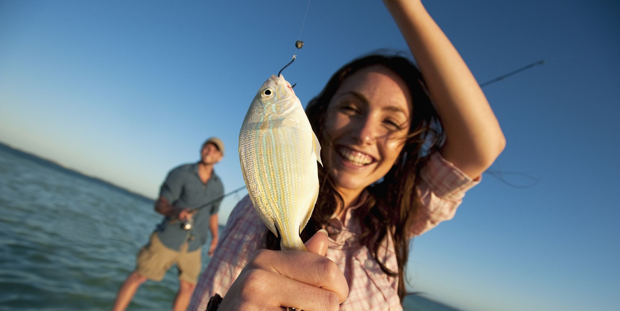 A woman smiles and holds up a small fish in Florida.