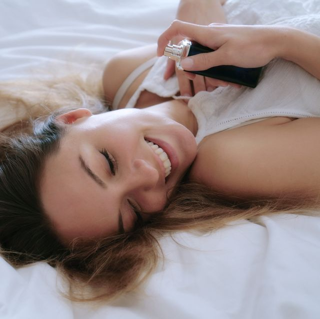 woman smiling holding perfume bottle