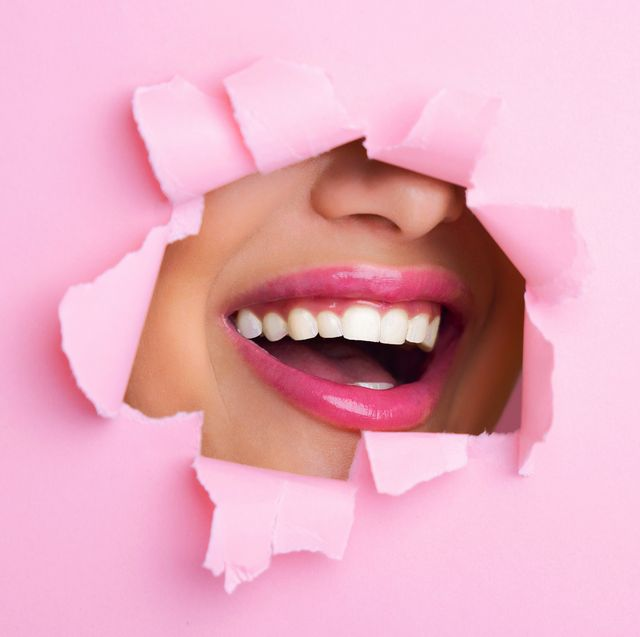 woman smiling through hole in pink paper