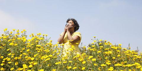 woman sneezing in flowers