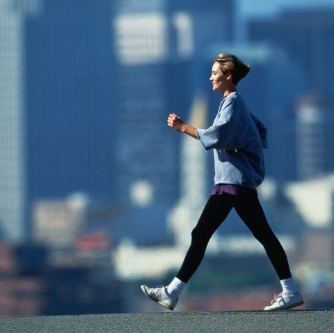 Woman speed walking in fore of city skyline