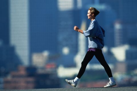 woman speed walking in fore of city skyline